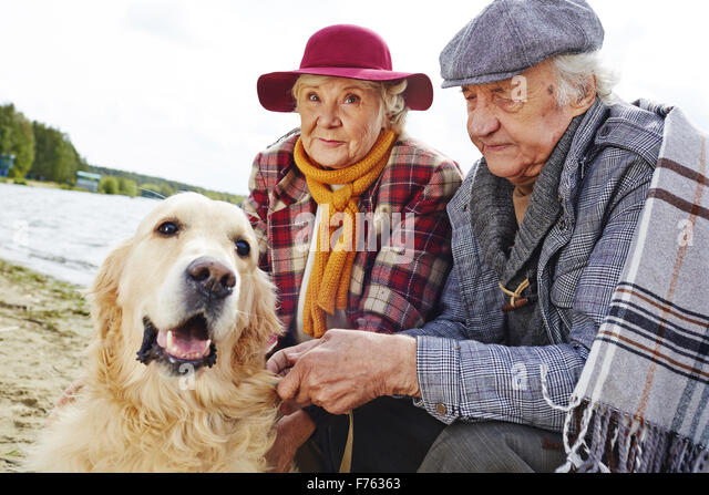 Retired couple and their pet enjoying weekend rest by seaside - Stock Image