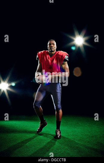 American football player holding ball - Stock Image