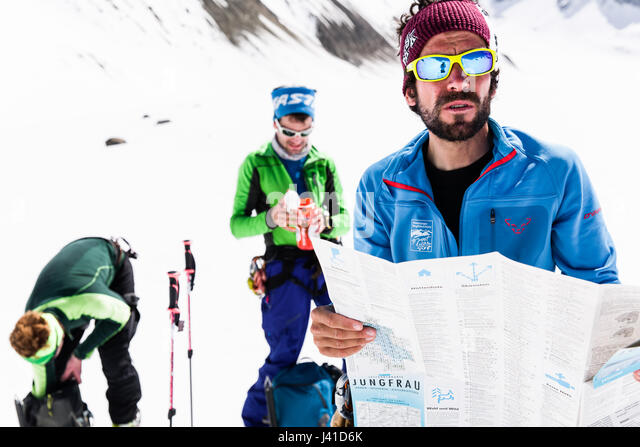 mountain guide checking the map for orientation, risk management with groups, Fiescher Glacier, Berner Oberland, - Stock Image