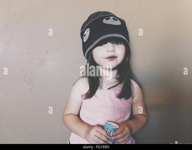 Portrait Of Cute Smiling Girl Holding Glass Indoors - Stock Image