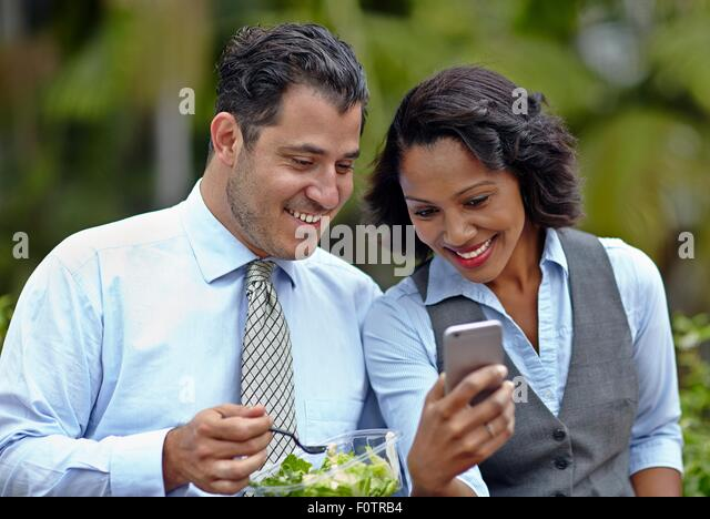 Business people sitting side by side enjoying a salad on lunch break, looking at smartphone, smiling - Stock Image