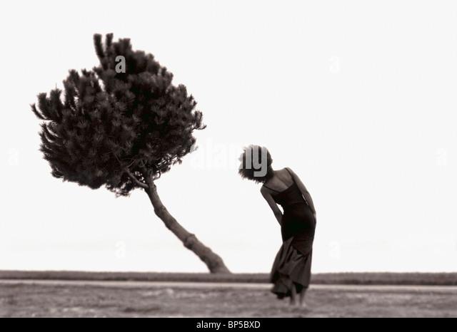 Woman in landscape bending body to imitate bending tree. - Stock-Bilder
