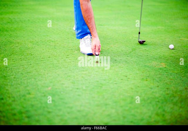 Golf player repairing divot on a green grass surface - Stock Image