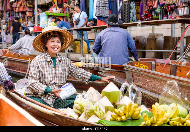 A merchant sales her goods at the Damnoen Saduak Floating Market outside of Bangkok. - Stock Image