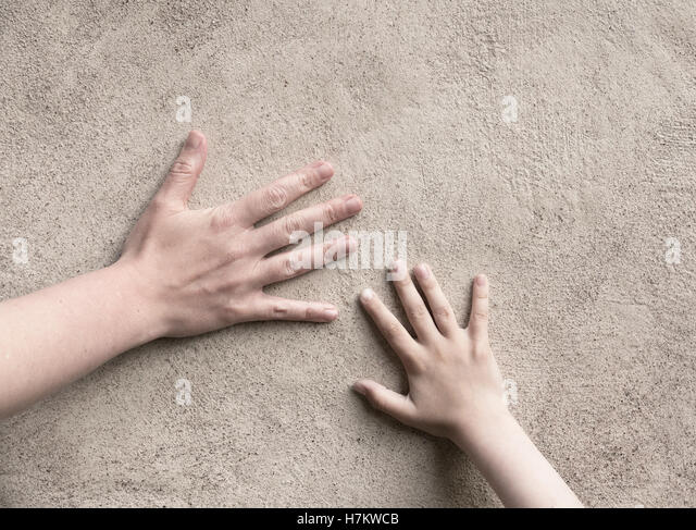 Two hands connecting. Adult and child hand meet, touching a wall. Conceptual image of connection between parent - Stock-Bilder