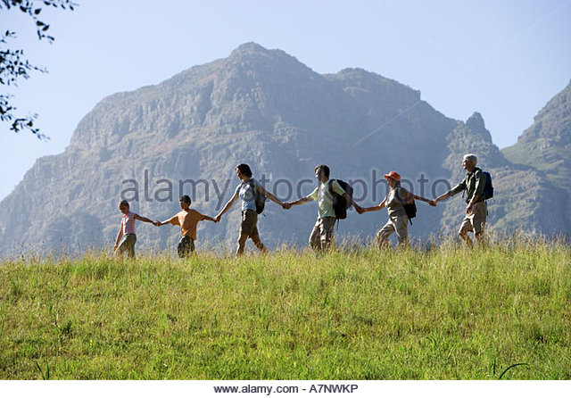 Multi generational family hiking on mountain trail walking in line all holding hands side view - Stock-Bilder
