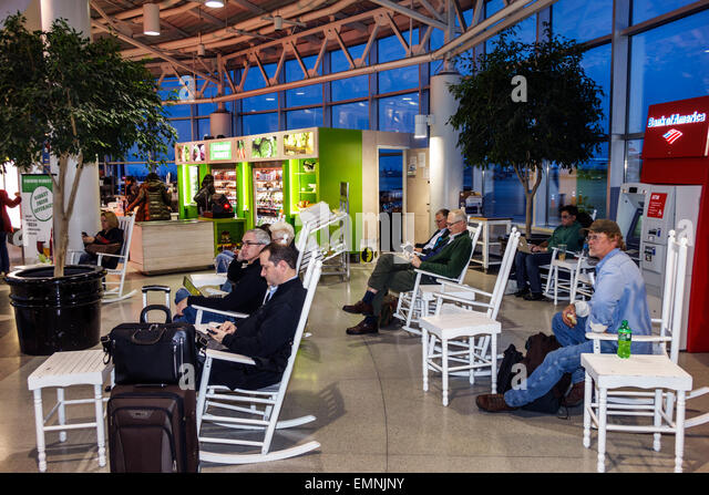 Charlotte North Carolina Charlotte Douglas International Airport CLT terminal concourse gate area rocking chairs - Stock Image