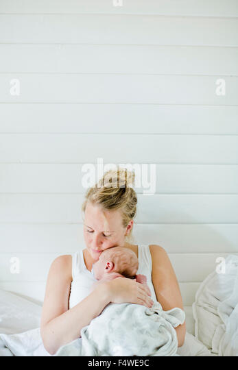 Mid-adult woman holding baby boy (0-1 months) in her arms - Stock Image
