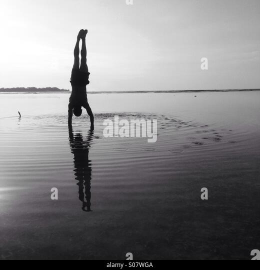 Handstand on the beach - Stock Image
