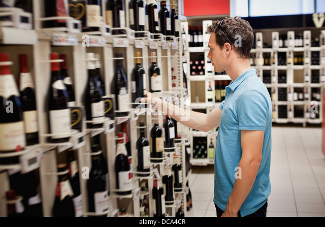 choosing wine in the shop - Stock Image
