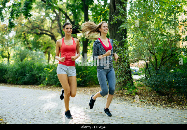 Young fit women jogging outdoors and staying fit - Stock Image
