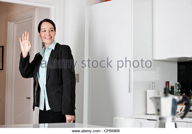 A woman leaving for work, waving goodbye - Stock-Bilder