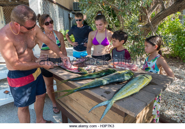 Family members watch a man gut fish. - Stock Image