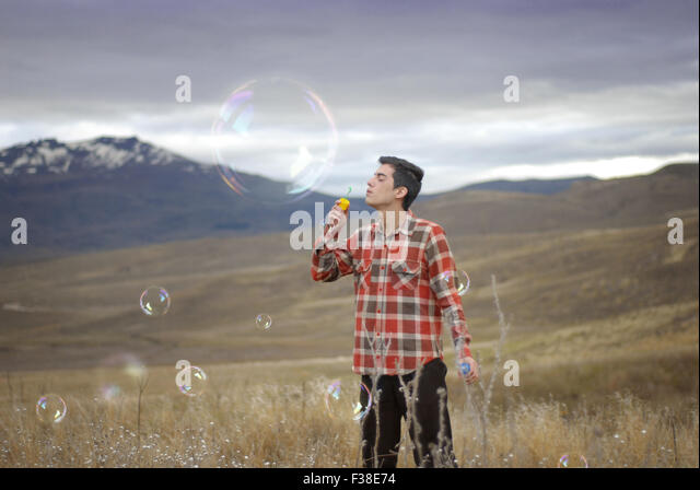 boy blowing a huge bubble - Stock Image