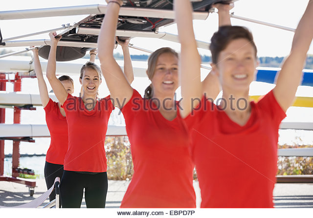 Rowing team carrying scull overhead - Stock Image