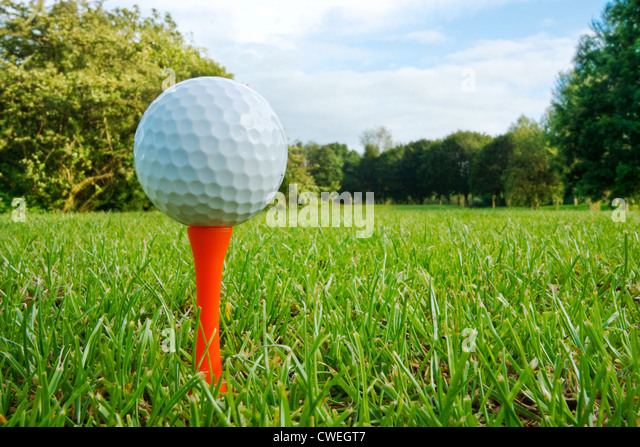 Golf ball on tee with fairway, golf course and flag in distance - Stock Image