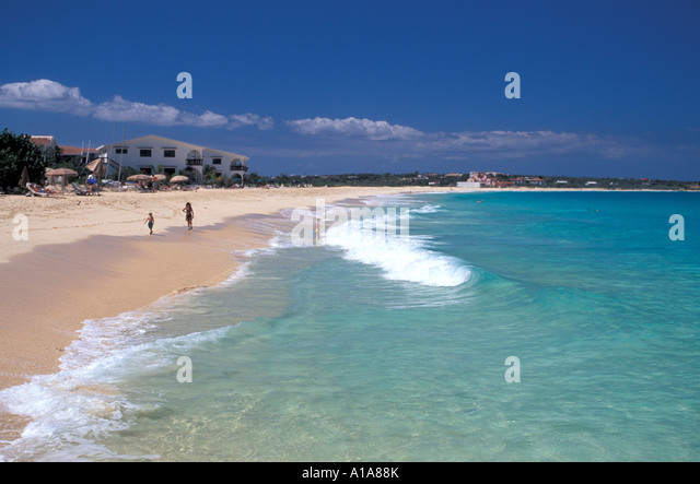 Anguilla beach Shoal Bay beach tourists walkinh in shoreline surf and blue green water of the caribbean sea - Stock Image