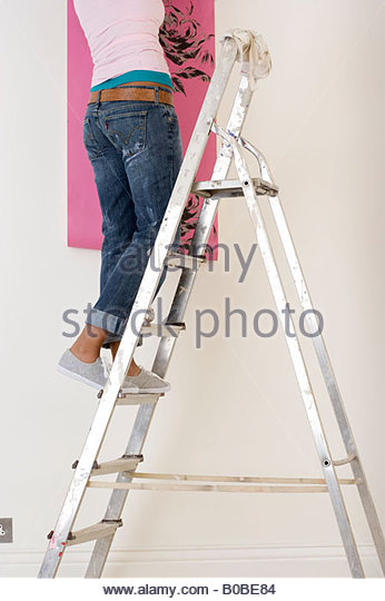 Young woman on ladder putting up wallpaper, low section - Stock Image