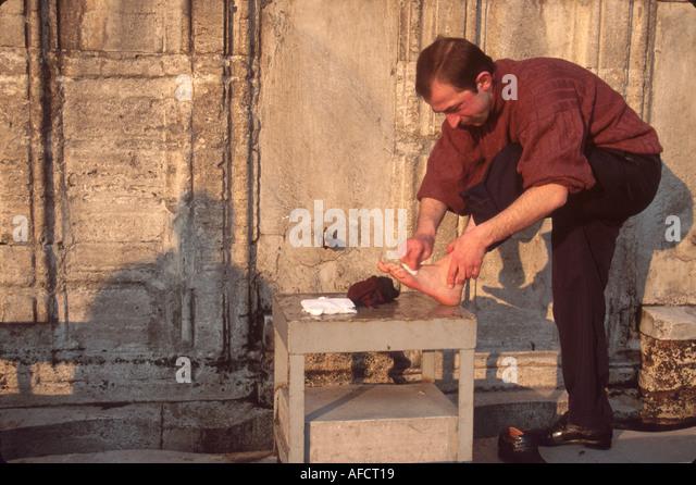 Turkey Istanbul Muslim man washes feet outside Sulemaniye Mosque built 1557 - Stock Image