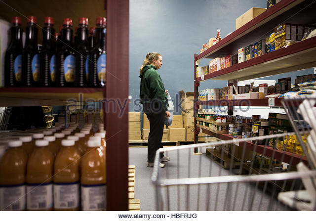 A woman chooses donated food and other items to take home to her family at the Jordan River Food Pantry. - Stock Image