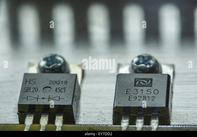 Two integrated circuits (ICs) screwed to an aluminium heat sink. The components come from a computer power supply - Stock Image