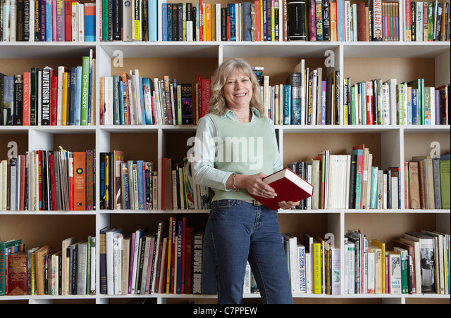Older woman holding book by bookshelves - Stock Image