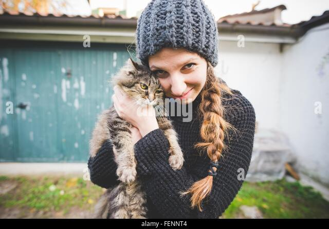 Young woman wearing knit hat snuggling cat, looking at camera smiling - Stock Image
