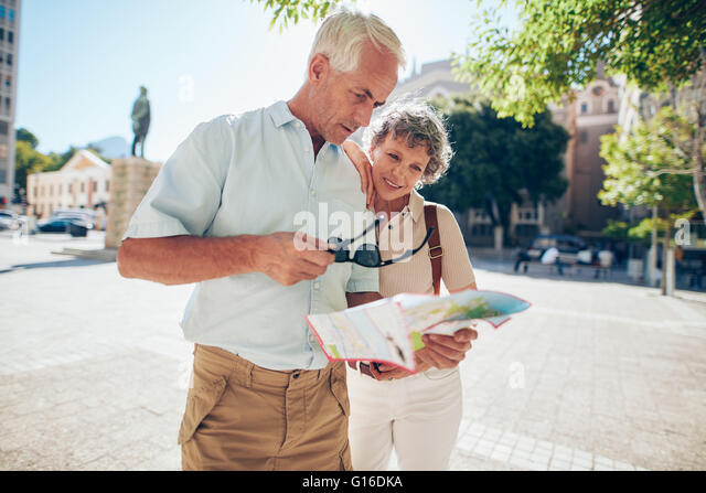 Mature couple standing outdoors in the city looking at a map. Senior man with his wife using city map for finding - Stock Image