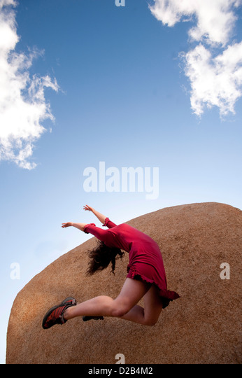 Female dancer in a red dress leaping up into an abstract sky-stone landscape. - Stock Image