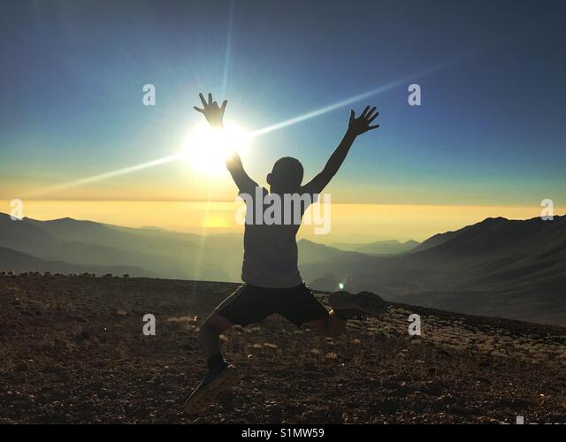 Silhouette of a kid jumping leaping happily on top of the Black Qorna mountain - Lebanon - Stock Image