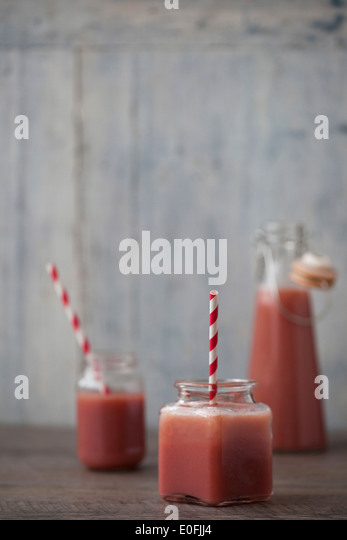 Strawberry Smoothies in jars with stripy straws - Stock Image