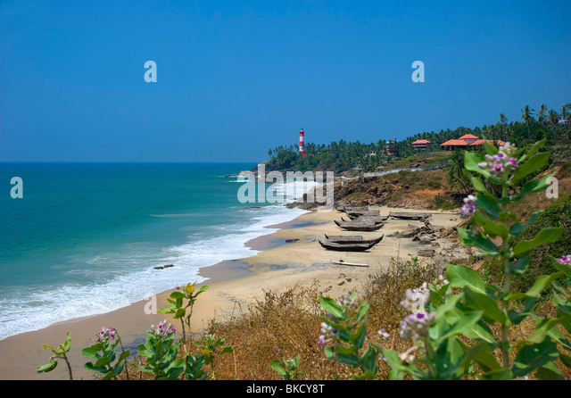 Fishing boats on Rockholm Beach with Lighthouse on headland, Kovalam, Kerala, India - Stock-Bilder