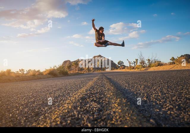 Man doing flying kick, Joshua Tree National Park, California, US - Stock Image