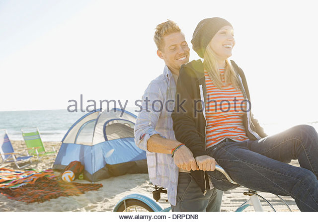 Smiling couple cycling on beach - Stock Image