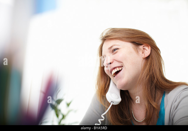 Happy girl on telephone at desk - Stock Image