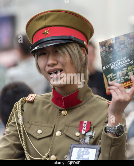 Young Woman in Imperial Japanese Army Service Uniform handing out leaflets in Akihibara, Tokyo, Japan - Stock Image