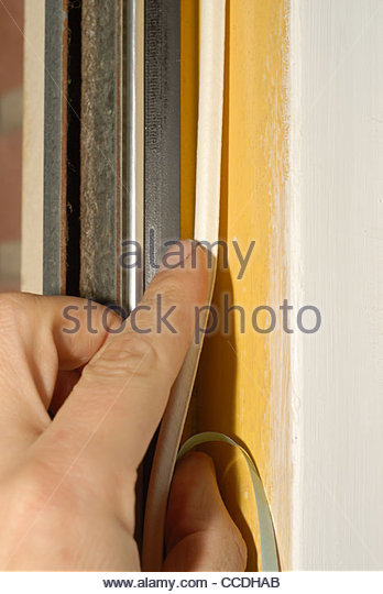 Close up - mans hand attaching self adhesive draught excluder around a front door - Stock Image