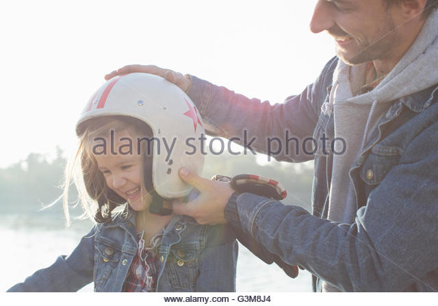 Father putting crash helmet on daughter's head, smiling - Stock Image