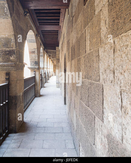 Angled view of one arch with interleaved wooden balustrades at the arcade surrounding the courtyard of caravansary - Stock Image