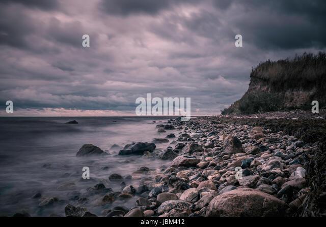 Tranquil rocks on ocean beach below stormy, overcast clouds, Bisserup, Denmark - Stock-Bilder