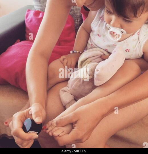 Mother nail polish to the small daughter - Stock-Bilder