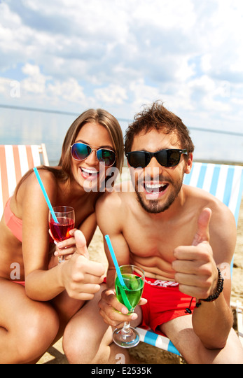 Joyful couple having fun at party on the beach - Stock Image