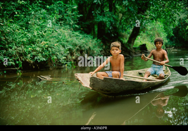 Boys in canoe in a small river in Tropical Rain Forest Amazon Region Para Brazil - Stock Image