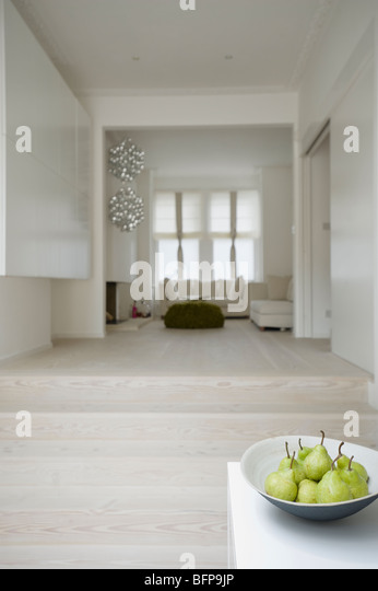 Open plan living area on split-level with pale wood floors - Stock Image