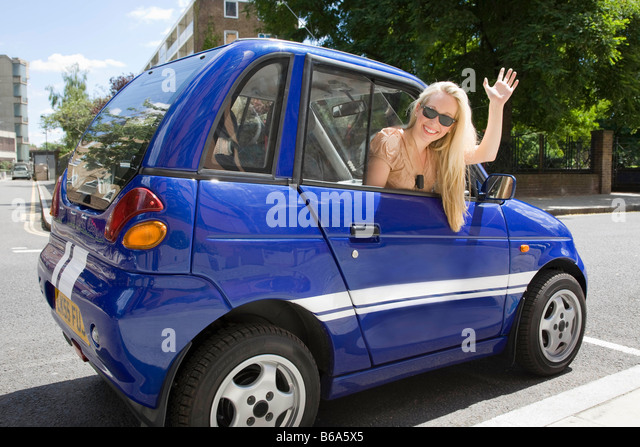 Young woman waving from electric car - Stock Image