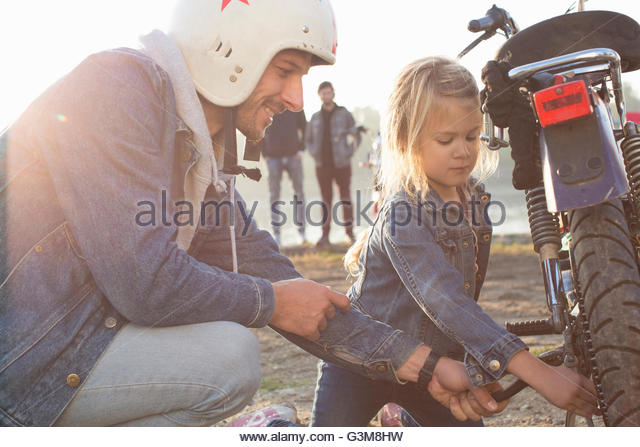 Young girl helping her father fix wheel on moped, outdoors - Stock Image