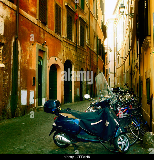 old street in the historic center of Rome with motor scooters and bicycles - Stock Image