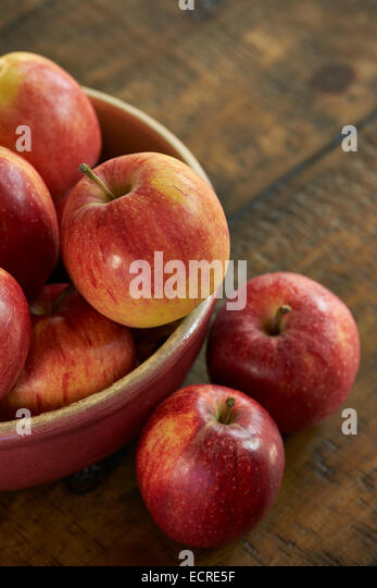 Fresh red apples in a bowel on a rustic wooden table. - Stock Image