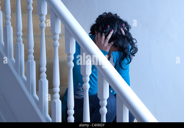 Young woman sitting alone on stairs hands on head. - Stock Image