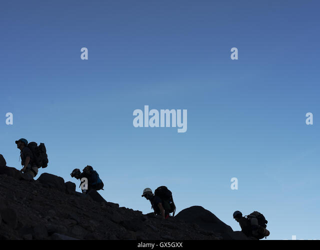 Hikers climb up a hill on their way to the summit of Mount Rainier - Stock Image